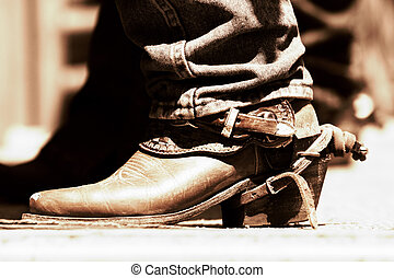 A rodeo cowboy's boots and spurs in high-contrast light and shadow (shallow focus copper tone).