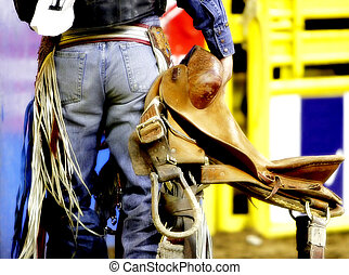 The backside of a rodeo saddle bronc cowboy as he carries his saddle before a competition (shallow focus, color saturated).