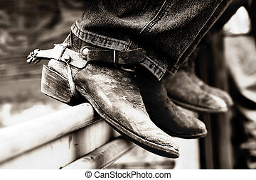 Experienced boots and spurs of rodeo cowboys sitting on a fence rail behind the scenes (shallow focus, high contrast black and white).