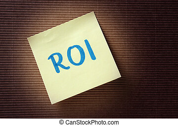 ROI (Return On Investment) acronym on yellow sticky note