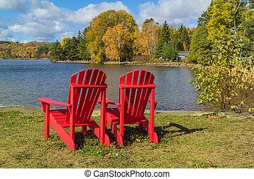 rojo, sillas de adirondack, en, un, orilla de lago