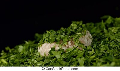 Roling fresh raw meat on chopped fresh parsley.