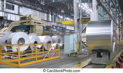 Roll of aluminum moves in production shop of rolling mill -...