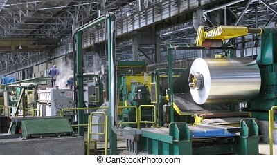 Roll of aluminum rotates on machine in shop on rolling mill,...