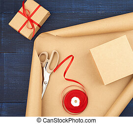 roll of brown kraft packaging paper, box tied with a red silk ribbon, scissors