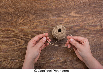 Roll of brown linen string on brown background