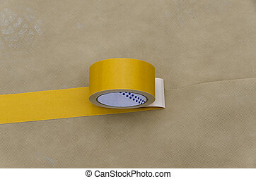 roll of double sided tape on the vapor barrier for the...