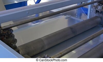 Roll of envelope for metal coating on industrial machine in factory.