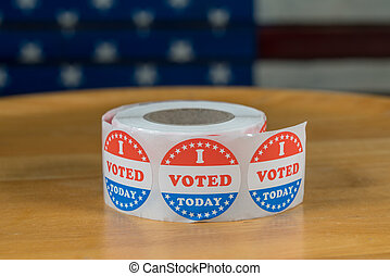 Roll of I Voted Today paper stickers on table with US Flag in background