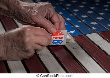 Roll of I Voted Today paper stickers on US Flag with hand removing one