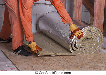 roll of mineral wool - worker cuts off a strip of mineral...