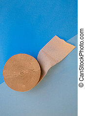 Roll of toilet paper on a blue background, top view