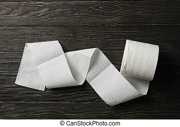 Roll of toilet paper on wooden background, top view