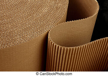 close up shot of corrugated packing material uncurling on black background