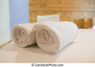 Roll of white towel on bed