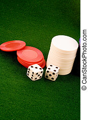 close up of two dice and three stacks of poker chips on green felt