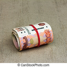 Roll Russian banknotes on a gray background closeup