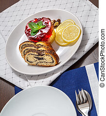 Roll with poppy, curd cake, lemon and nuts on a plate