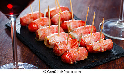 Rolled bacon with sausages on black dish. High quality photo