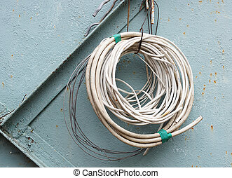 Rolled cables on the background of old metal wall.