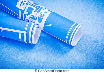 Rolled engineering drawings on blue background construction conc