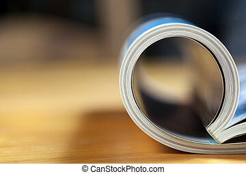 Rolled Magazine - Glossy magazine with pages rolled over, on...