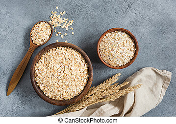 Rolled oats and oat flakes in wooden bowl