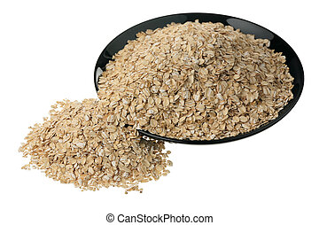 Rolled oats in a black ceramic plate on a white background