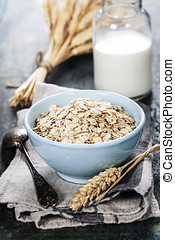Rolled oats in a bowl and milk on wooden board