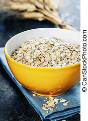 Rolled oats in a bowl on wooden board