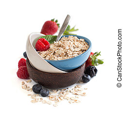 Rolled oats in a bowl with berries isolated on white