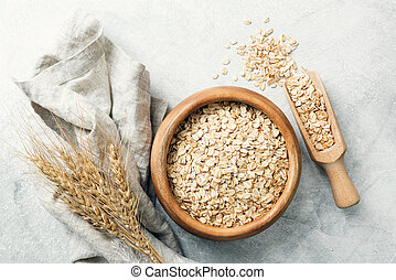 Rolled oats in wooden bowl and ears of wheat