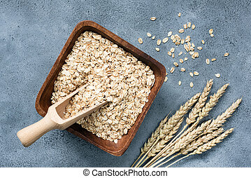 Rolled oats in wooden bowl on concrete background