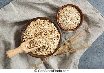 Rolled oats, oat flakes in wooden bowl