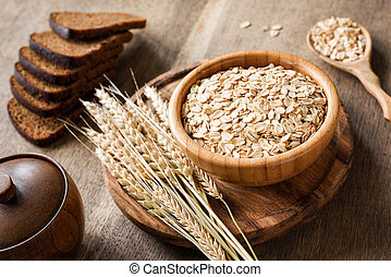 Rolled oats or oat flakes and golden wheat ears on wooden background.