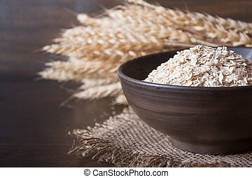 Rolled oats or oat flakes in bowl and wheat ears on wooden board. Healthy eating, vegan food concept.