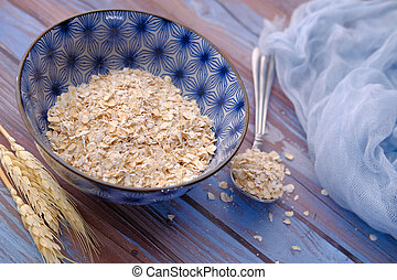 Rolled oats or oat flakes in wooden bowl on table