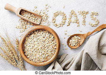 Rolled oats or oat flakes in wooden bowl on white background