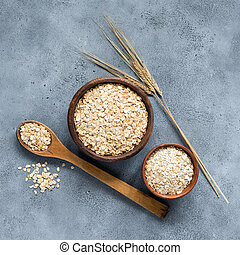 Rolled oats or oat flakes in wooden bowl, top view