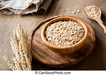 Rolled oats, organic oat flakes in wooden bowl and golden wheat ears on wooden background