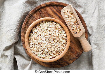 Rolled oats, organic oat flakes in wooden bowl on wooden background. Table top view