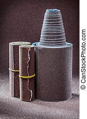 rolled sandpaper on abrasive background close up
