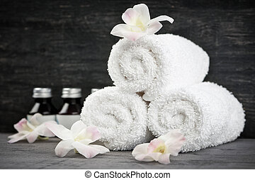 White rolled up towels with body care products at spa