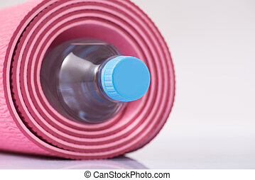 Rolled up yoga mat with bottle of water inside.