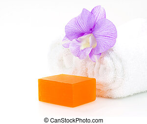 Rolled white towel, soap and orchid