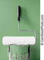 Clean paint roller on top of khaki green paint can for home diy decorating