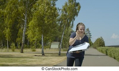 Busy pizza delivery woman talking on phone with customer while rollerblading at speed hurry deliver order. Female roller working in fast pizza delivery service and riding with pizza box in public park.