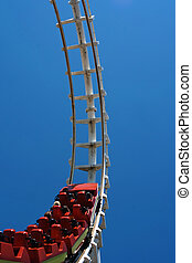 Bright red roller coaster beggining entry to loop.