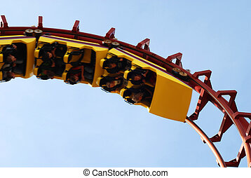 Roller Coaster with people taking a ride.
