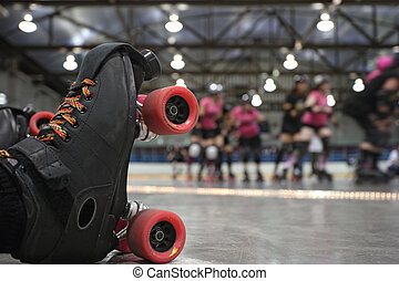 An abstract image of the roller-skates of a fallen skater as her teammates in the background continue to skate around the track of the roller derby.